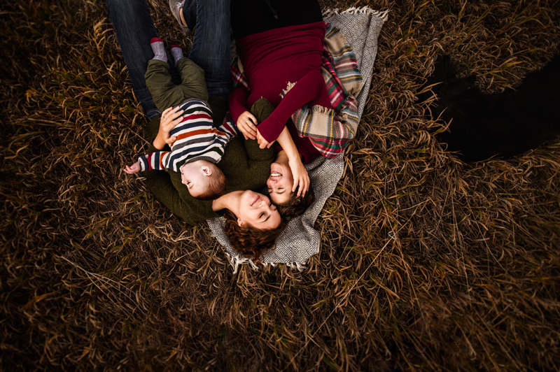 Family Photographer, two women lay snuggled together on a blanket in the grass, one of them holds a baby boy