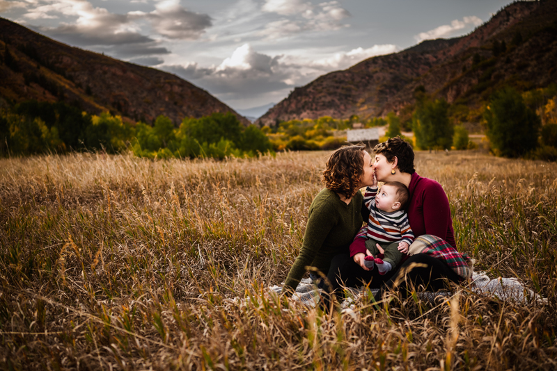 Family Photographer, two women kiss in grassy field as they hold their baby son