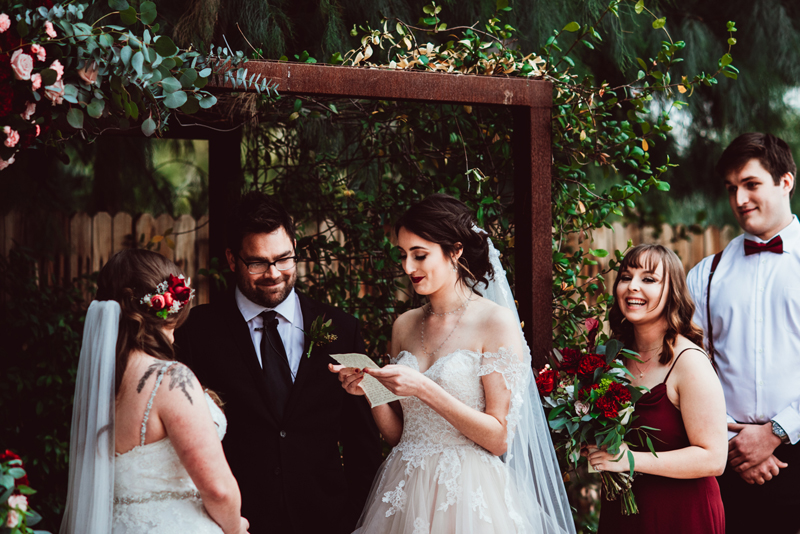 LGBTQ+ Wedding, two happy teary-eyed brides exchange vows as the officiant and spectators all smile