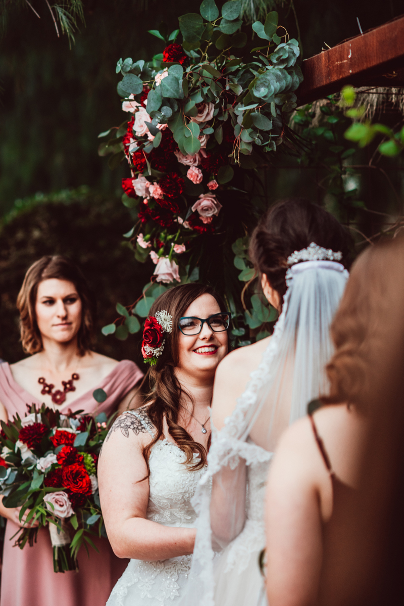 LGBTQ+ Wedding, two brides exchange vows before bridesmaids, roses all around in the backdrop