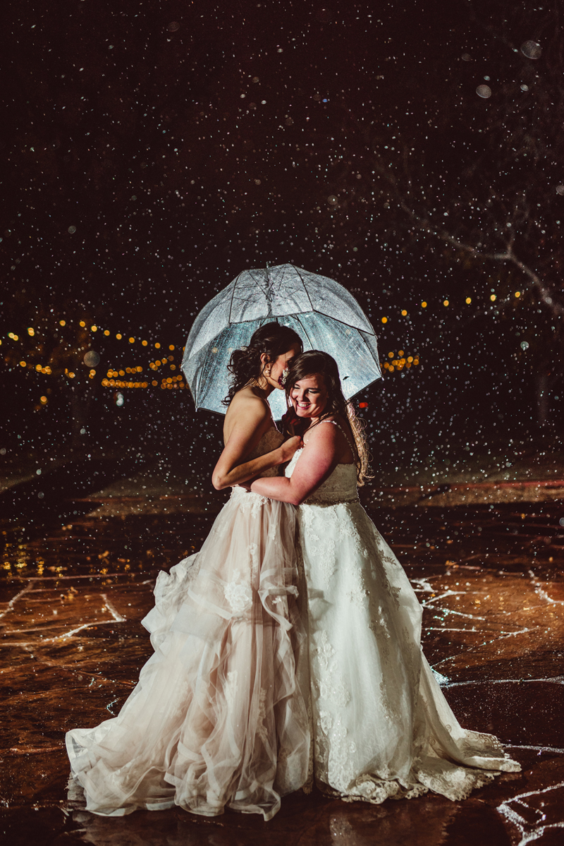 LGBTQ+ Wedding, two women in wedding dresses hold each other close under an umbrella on a magical snowy day