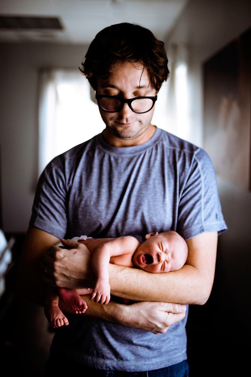 Family Photographer, young father looks down and admires his sleeping baby, he is almost serious in his thick framed glasses