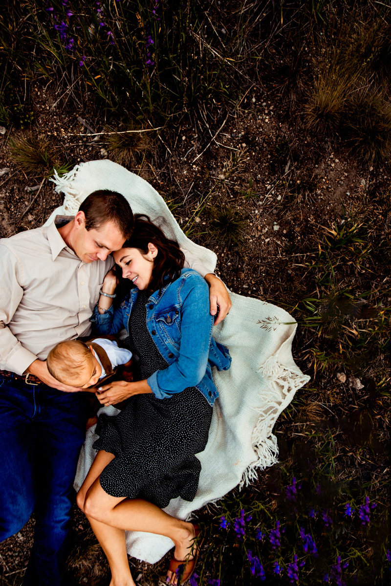Family Photographer, young family of three laying on blanket in grass