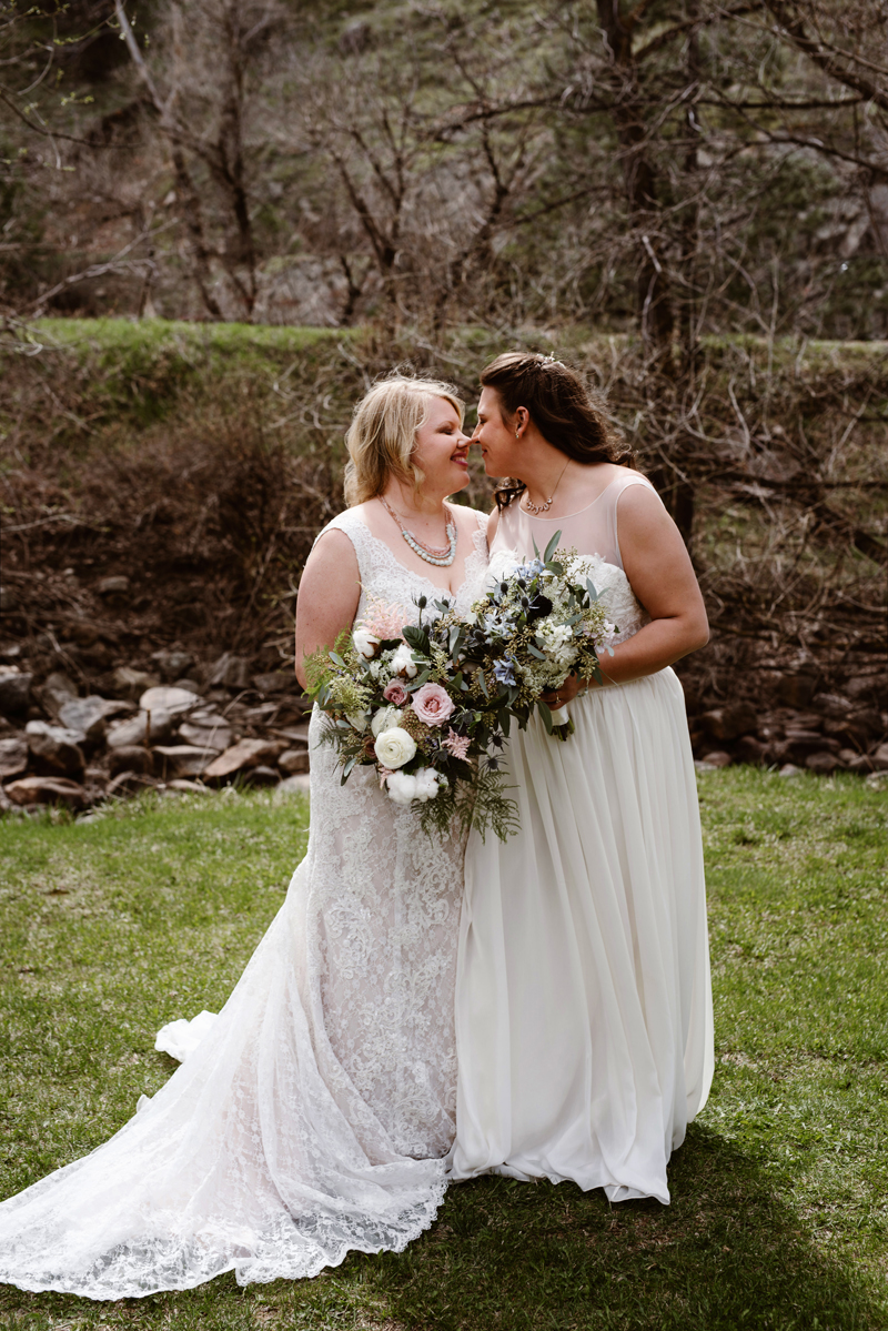 LGBTQ+ Wedding, two women smiling nose to nose in their wedding dresses