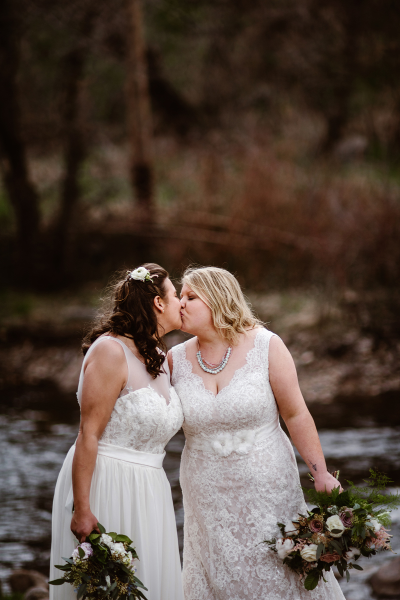 LGBTQ+ Wedding,  two brides kiss in their weeding dresses holding bouquets near a river