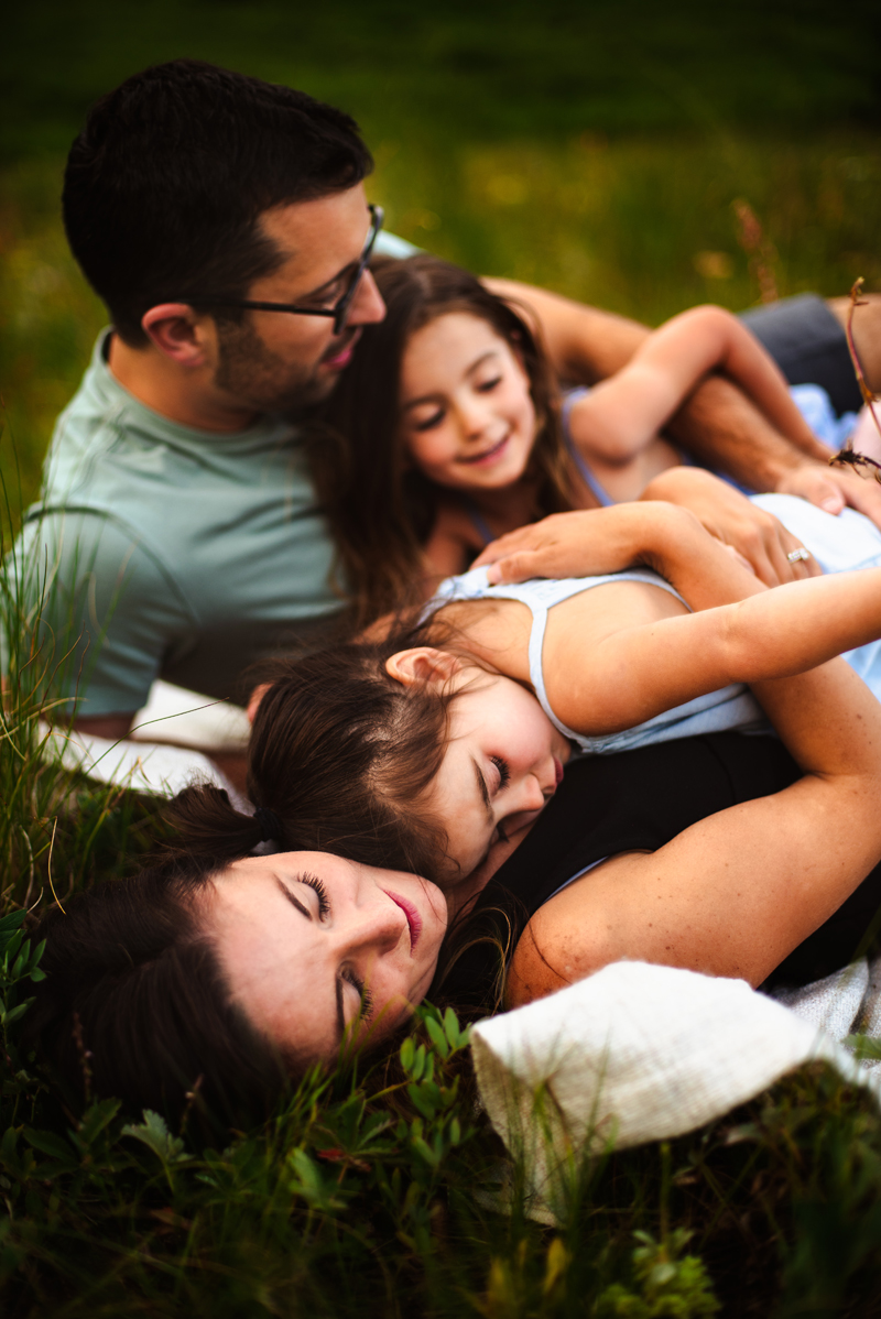 Family Photographer, mom and dad lay in the grass as they snuggle their young daughters