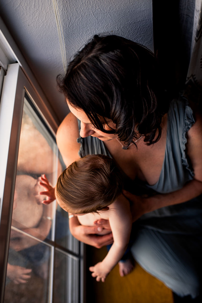Family Photographer, woman sits looking out window with baby, baby's hand on the glass