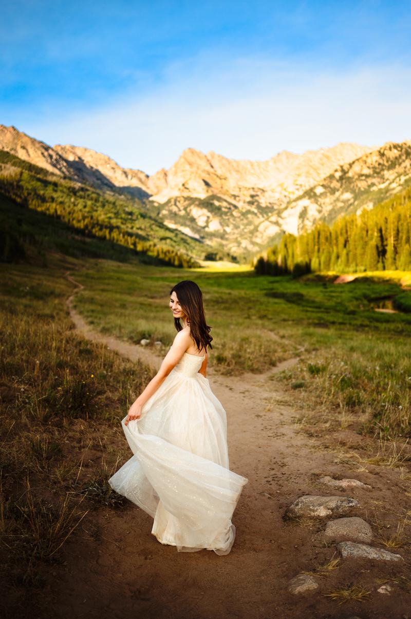 Senior Portrait, High School woman in white dress walks along mountain trail