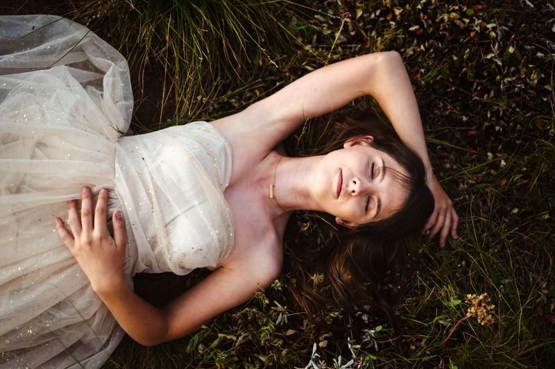 Senior Portrait, High School woman lays in grass, in a white dress, eyes closed and happy