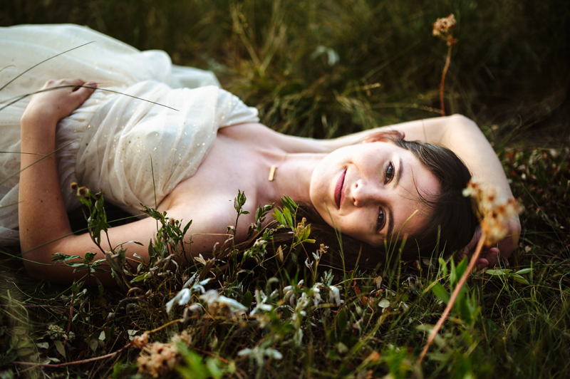 Senior Portrait, High School woman lays in grass smiling, she wearing white lacy dress