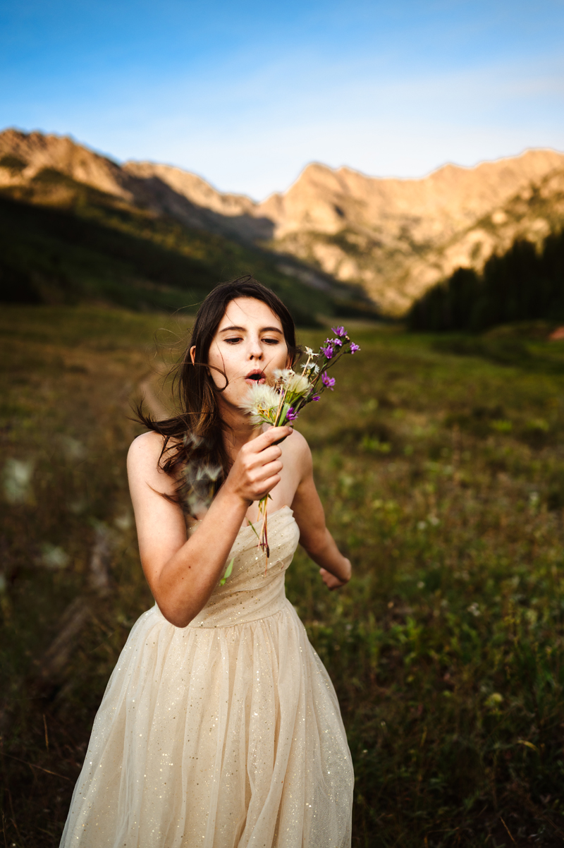 Senior Portrait, High School woman in a white dress blows into her bouquet of wild flowers in the mountains