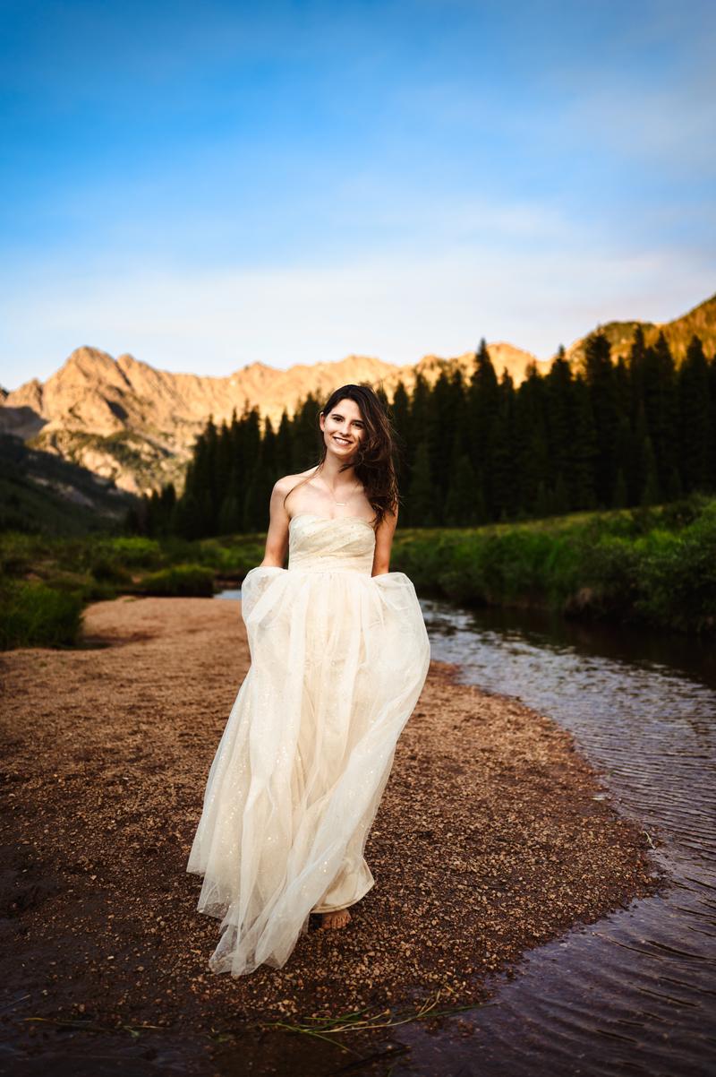 Senior Photographer, teen girl in long white dress next to a river