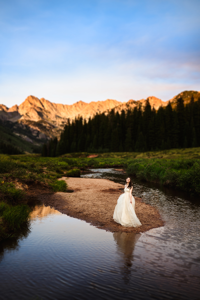 Senior Portrait, High School woman in white dress stands near streams in the mountains