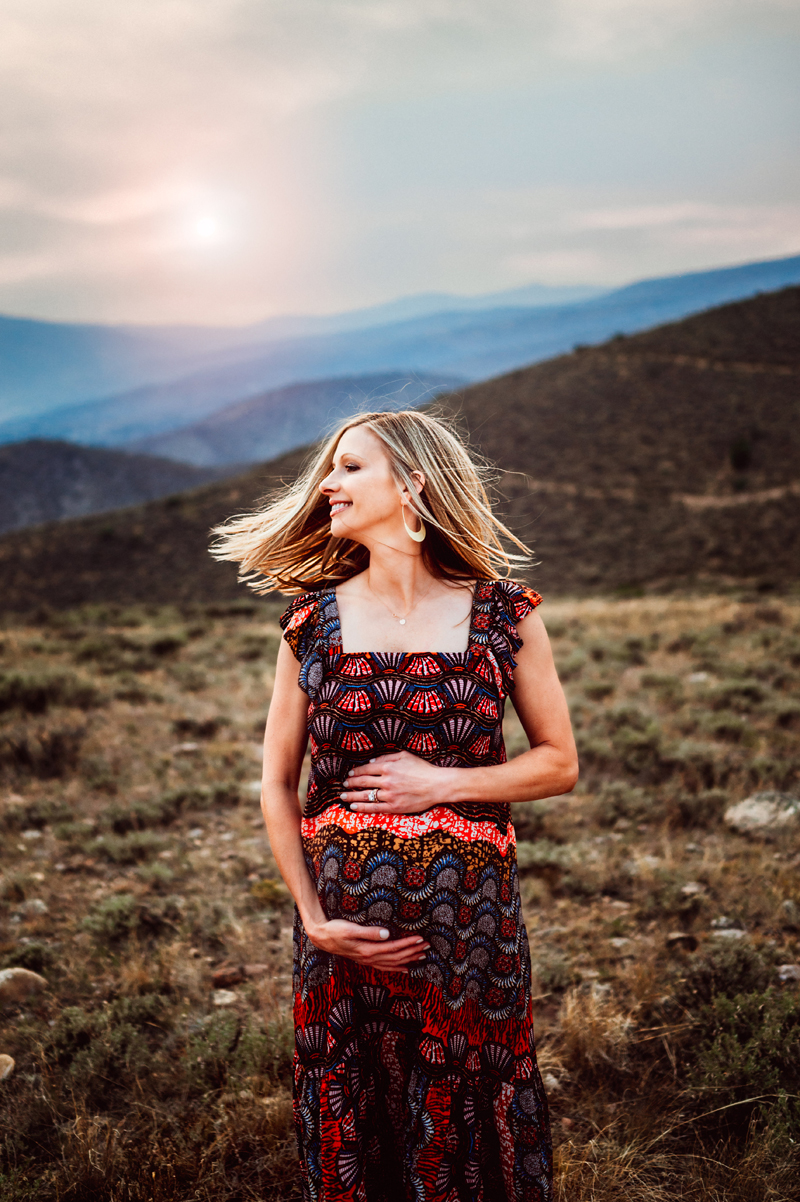 Maternity Photography, smiling blonde woman on a hillside holds her pregnant belly