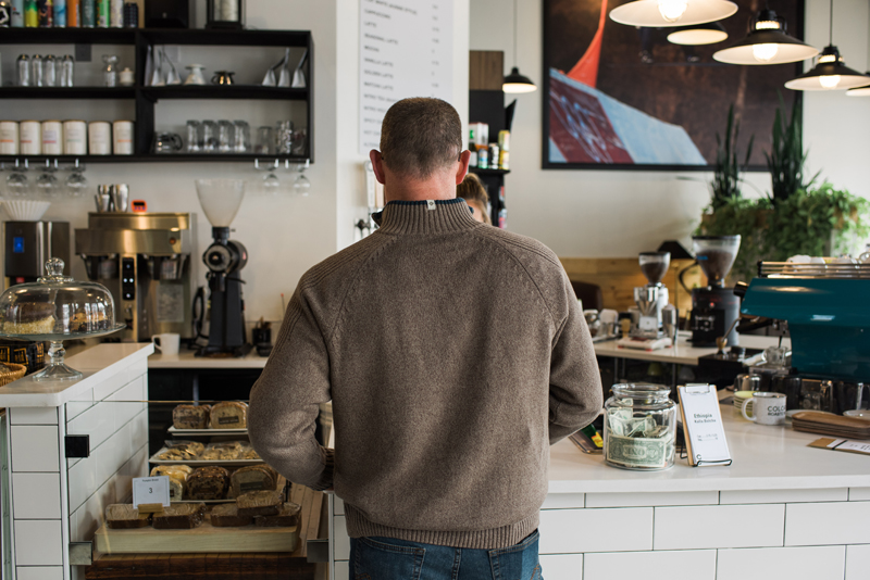 Business Photography, man in a knit sweater checks out at a trendy coffee shop