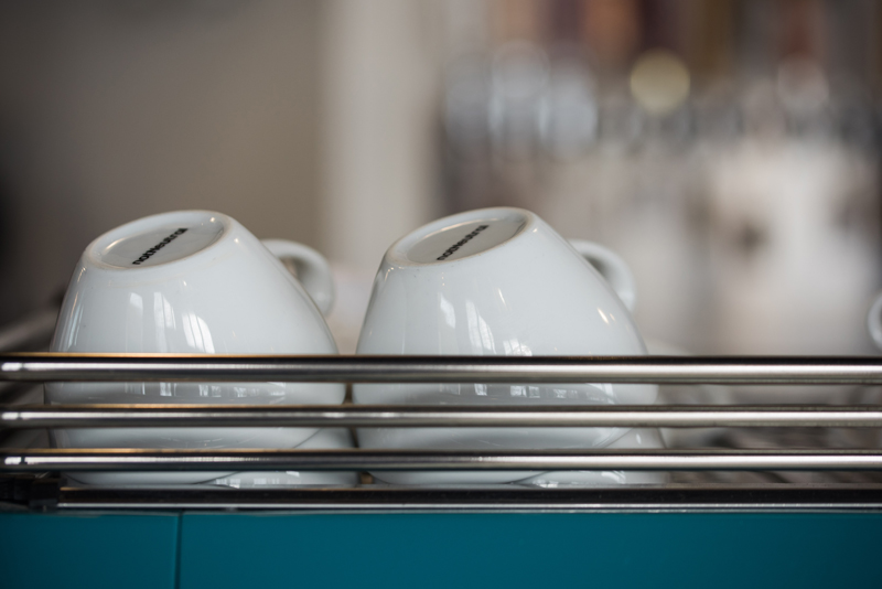 Business Photography, two stacks of ceramic white cappuccino mugs sit atop a blue espresso machine