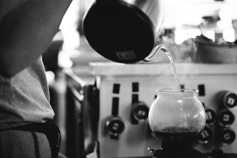 Business Photography, Black and White photo of hot water kettle pouring hot water in a pour over for a fresh cup of coffee