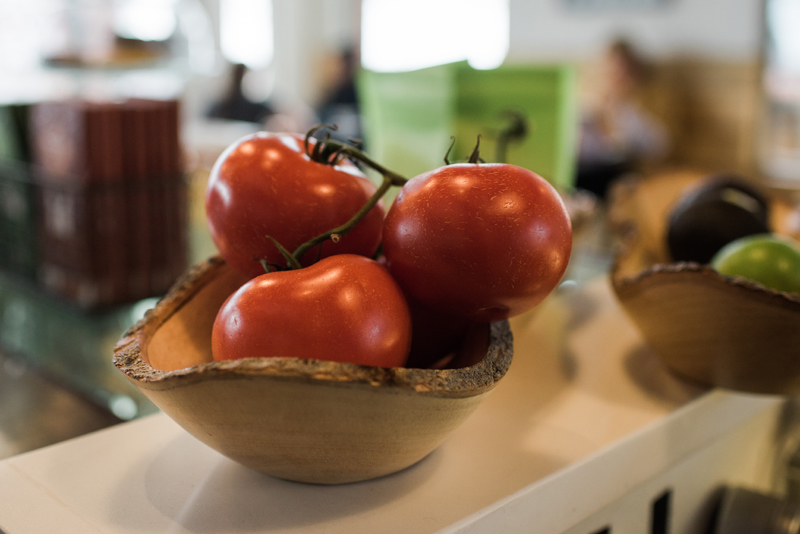 Business Photography, a bowl of tomatoes sits in a crafted wooden bowl atop a store ledge, people sit in the blurred background