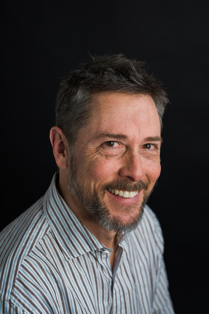 Business Photography, A headshot portrait of a man in his late forties smiling, dressed in business casual attire, he has a trimmed beard and dark hair