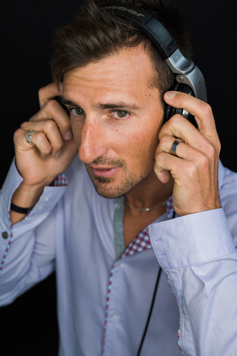Business Photography, professional headshot of a dark haired man in his thirties, he holds professional headphones to his ears