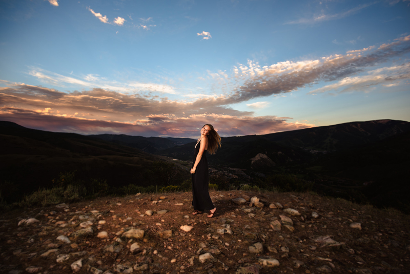 Senior Portrait, High School woman in dark dress looks back and smiles at dusk on a mountain trail