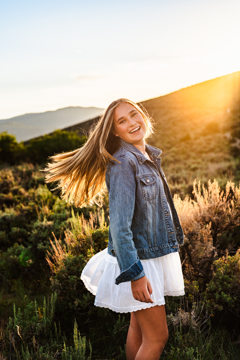 Senior Portrait, High School blonde woman in blue jean jacket and a white dress smiles before a hilly meadow
