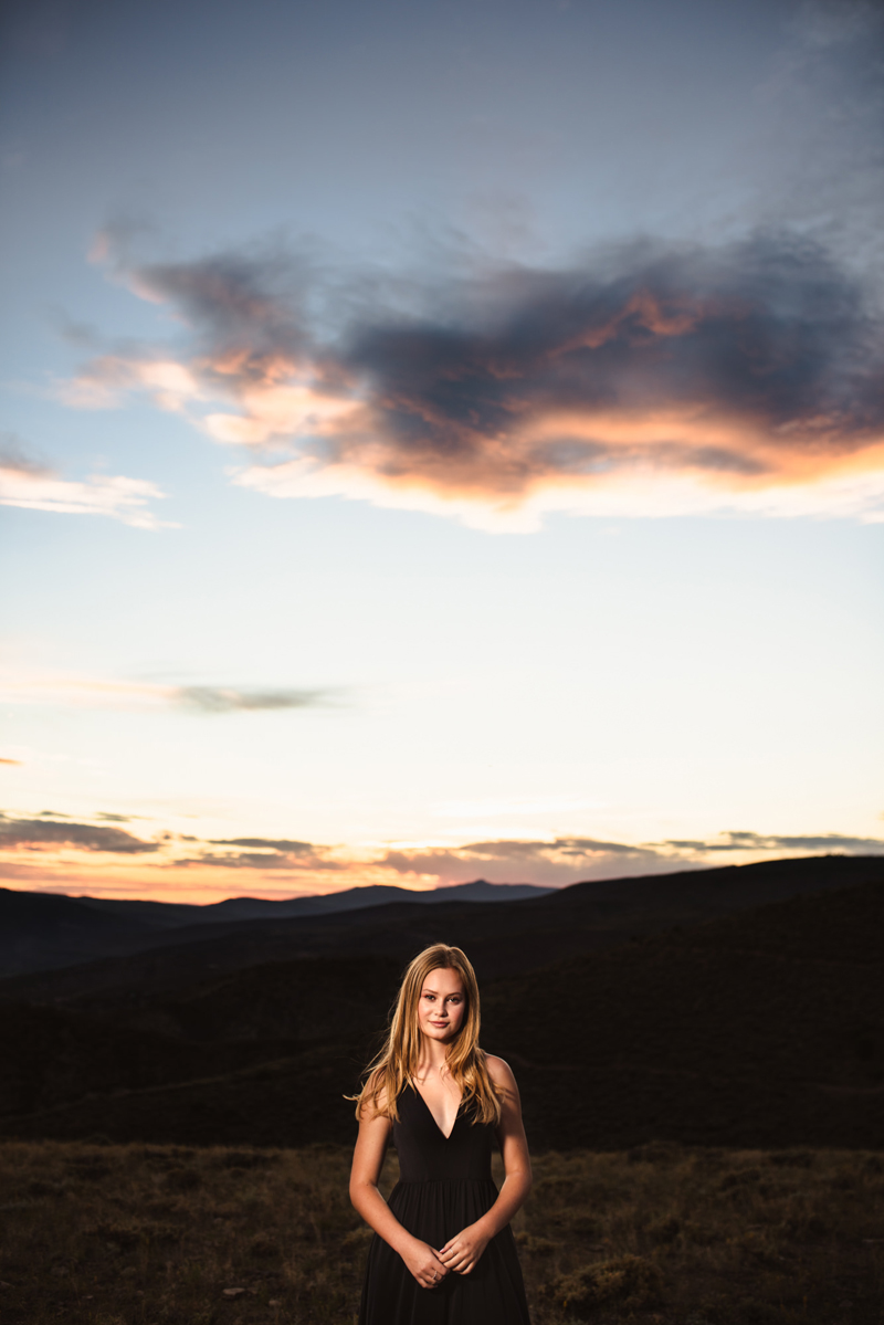 Senior Portrait, High School blonde woman in a Burgundy dress stands confidently with mountains behind her