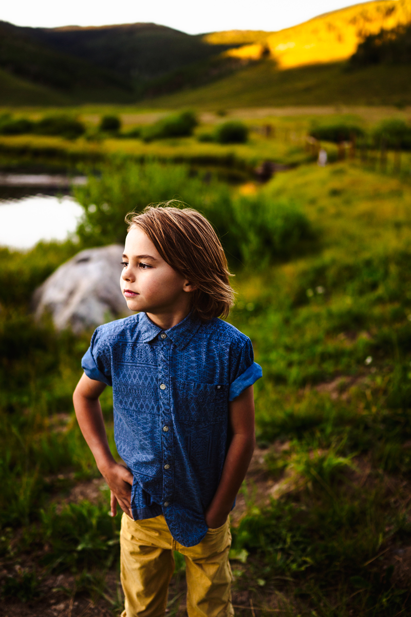 Family Photographer, five year old boy with long hair and blue polo stands in grass
