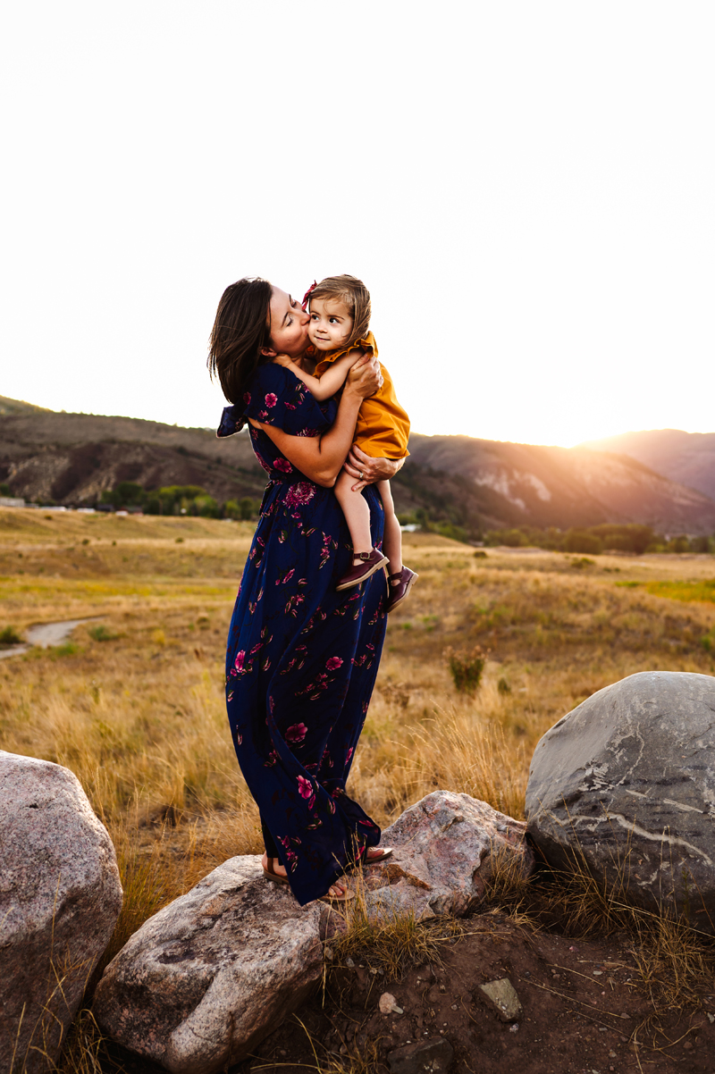 Family Photographer, a mother in a dark flora dress kisses her toddler daughter on the cheek, the girl enjoys it