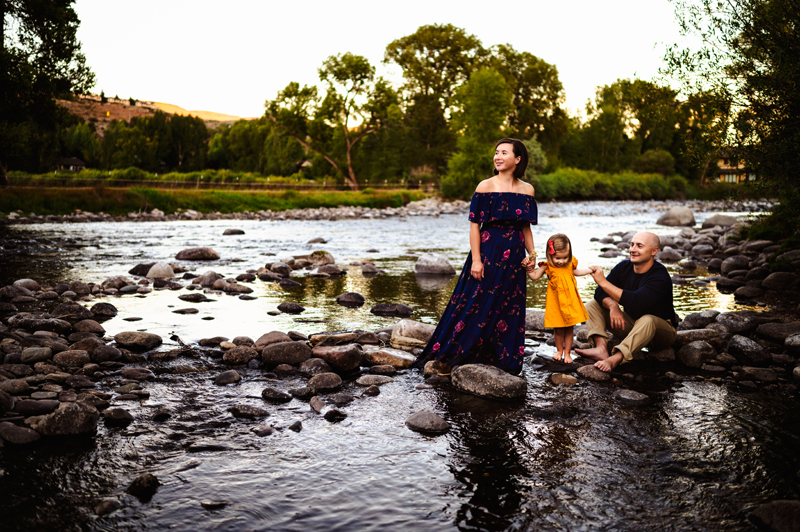 Family Photographer, Mom and dad hold daughters hand as the stand in a quite river