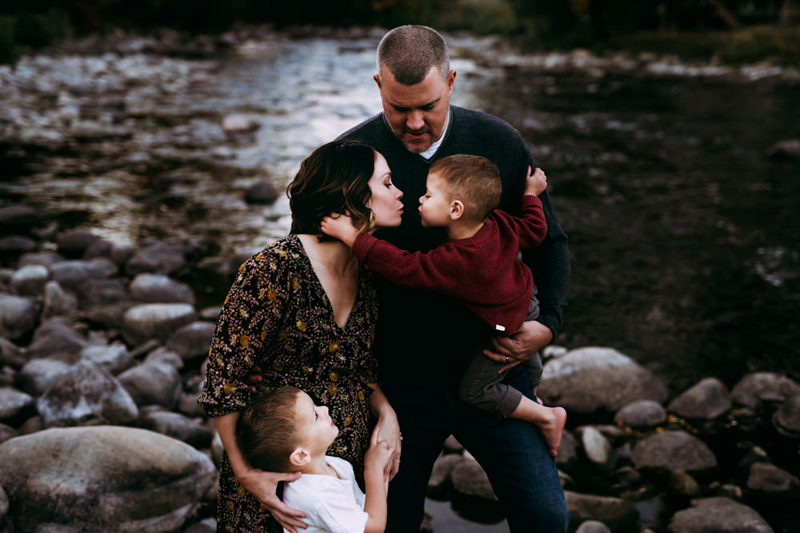 Family photography, family of four stands before river, a son reaches over to kiss mom