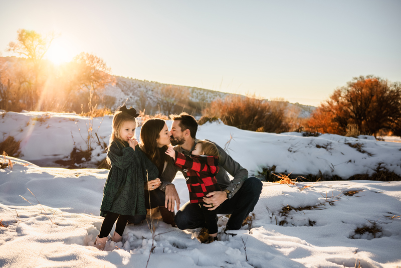 Family Photographer, a mom and dad kiss in the snow while they hold their two young children close, a boy and a girl