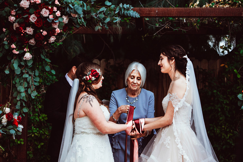 LGBTQ+ wedding, two brides look into each other's eyes as an elderly woman wraps red ribbon around the their joined hands