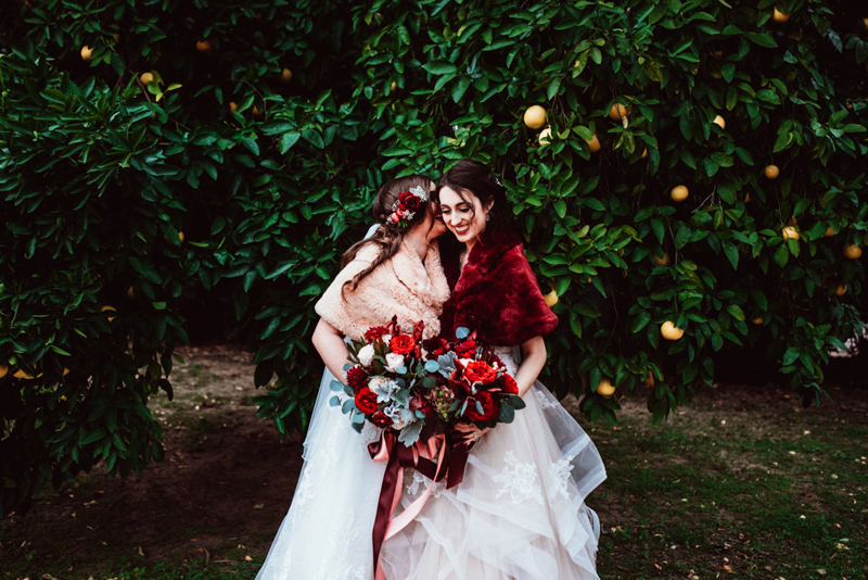 LGBTQ+ Wedding, two brides laugh as one whispers into these ear in an orange grove