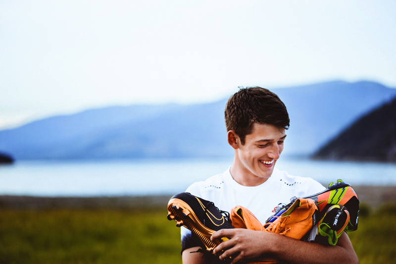 Senior Portrait, outdoors, a High School man wearing soccer jersey holds cleats and smiles