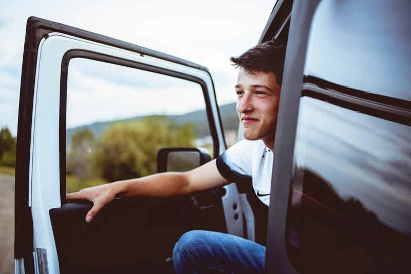 Senior Portrait, High School Man sits opening door to driver side of White Jeep