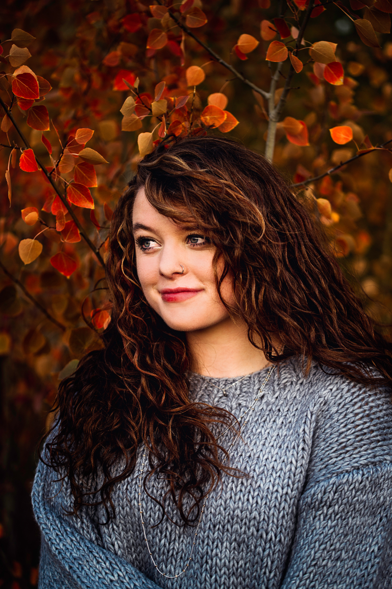 Senior Portrait, High School woman smiles before trees full with fall leaves