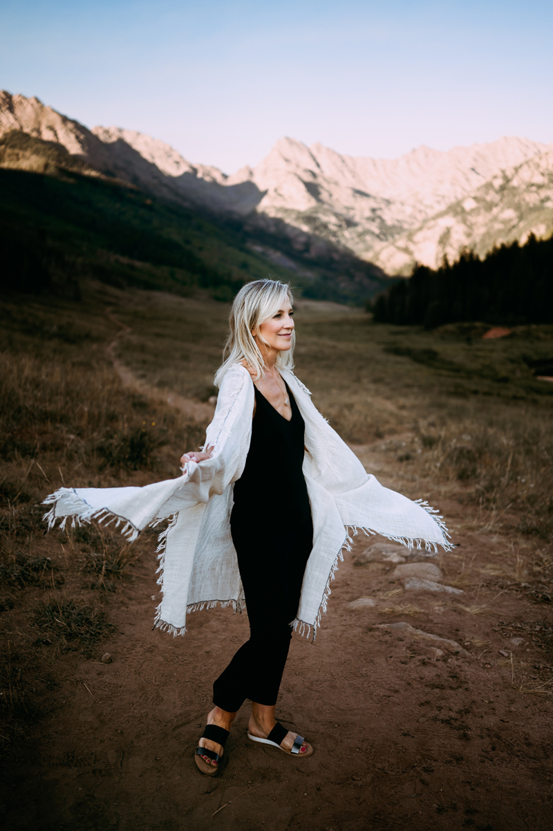 Business photography, blonde woman on mountain trail happily spins, white poncho sweater twirls with her