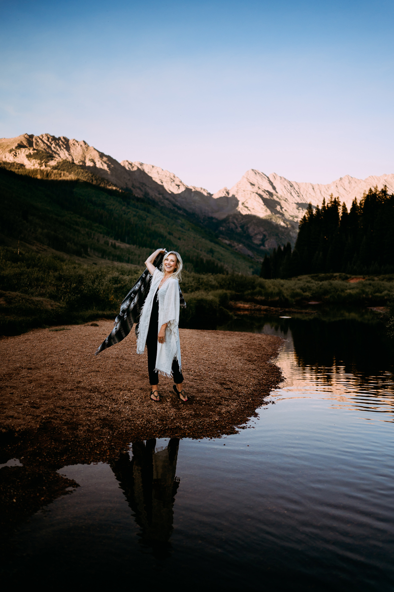 Business Photography, Smiling woman holds up a black and white poncho blanket in the air as if to throw it, she stands in front of a mountainous background near a stream
