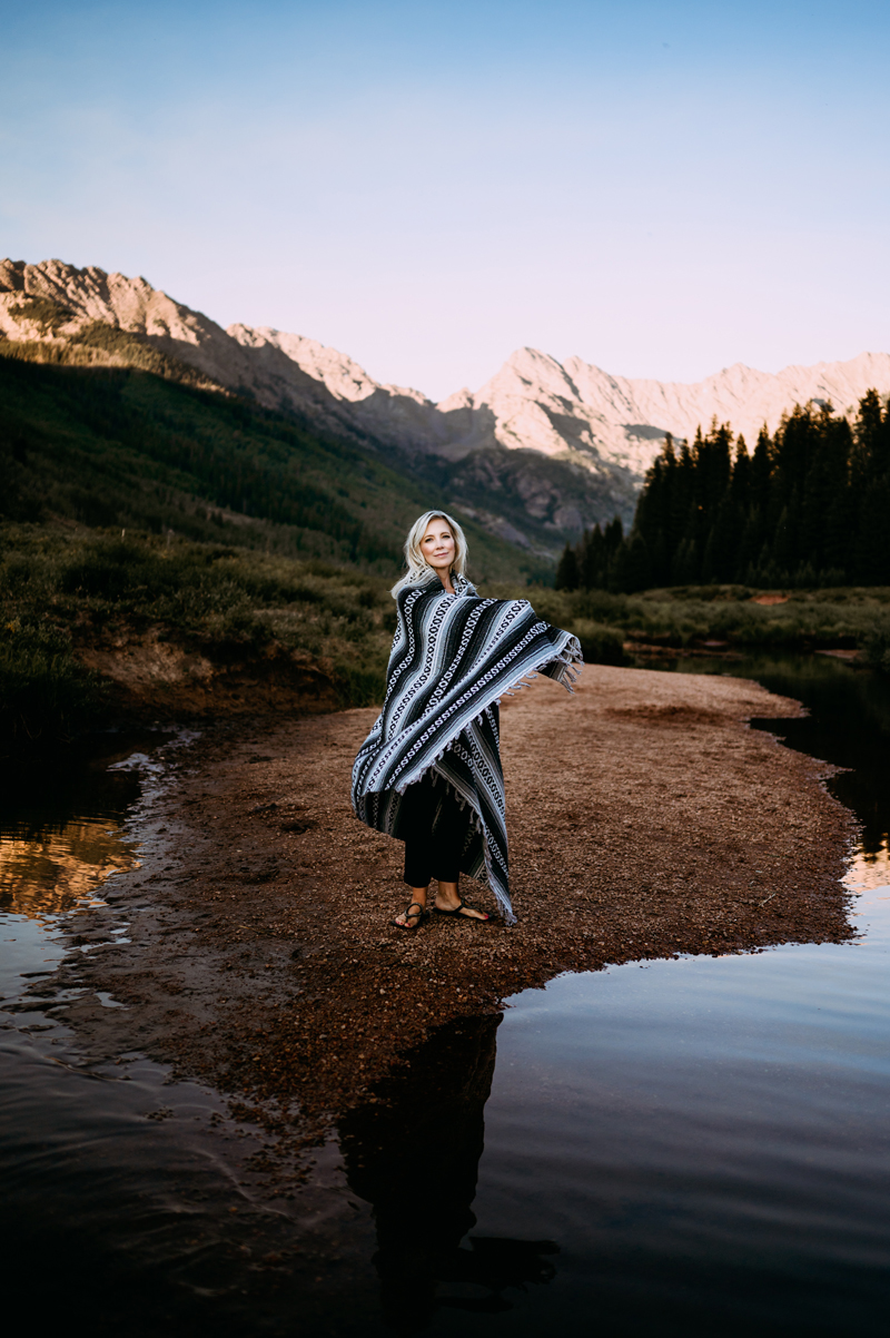 Business Photography, A woman spins in a poncho style blanket, She stands next to a quiet river, there are mountains in the background