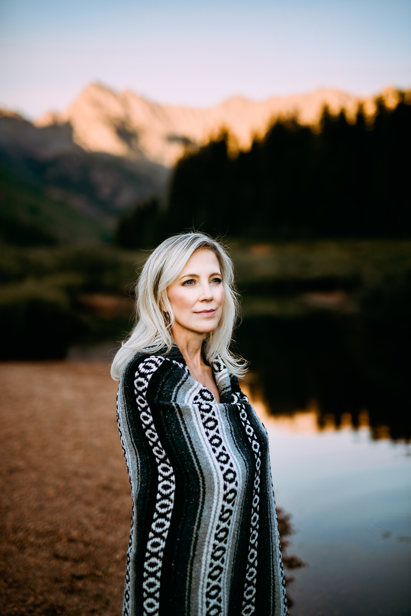 Business Photography, Woman is wrapped in a poncho blanket with native American design, she is outdoors near a river in the mountains at dusk