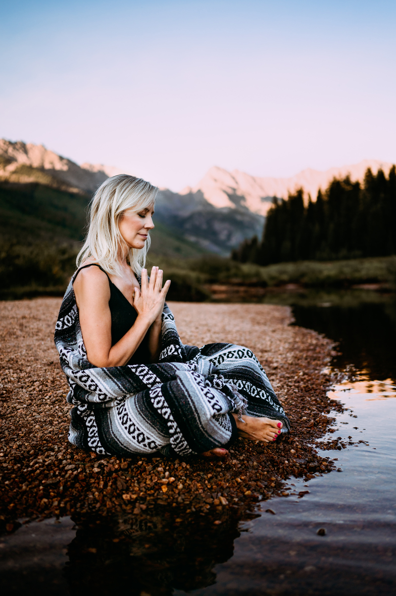 Business Photographer, woman meditating next to river