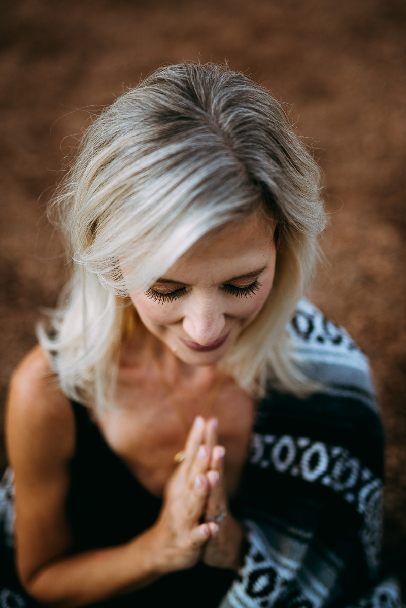 Business Photography, close-up portrait of a blonde woman with hands together to pray or meditate, she wears a black tank