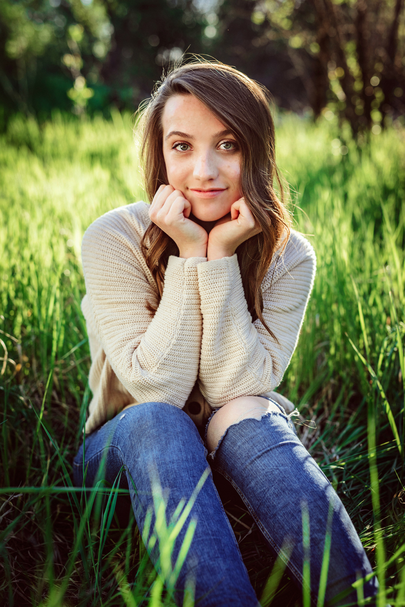 Senior Portrait, High School woman wearing a knit beige sweater and blue jeans sits in the grass