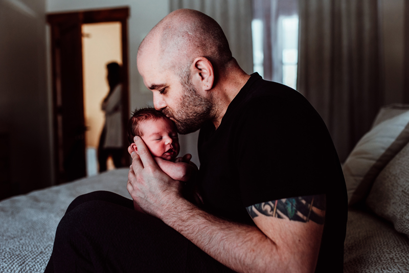 Family Photography, father kisses newborn baby son as he holds him on bed