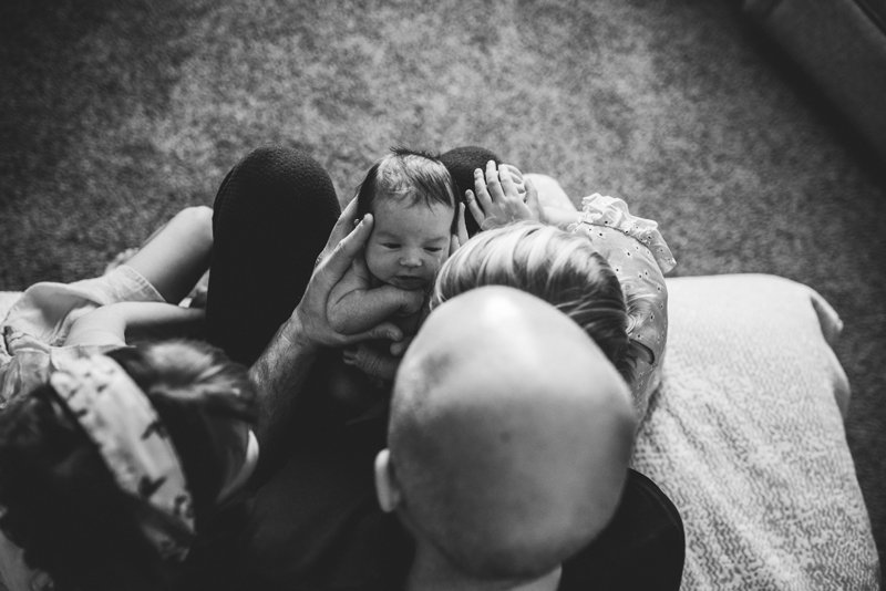 Family photography, a mother, father, and daughter, all look down at newborn baby