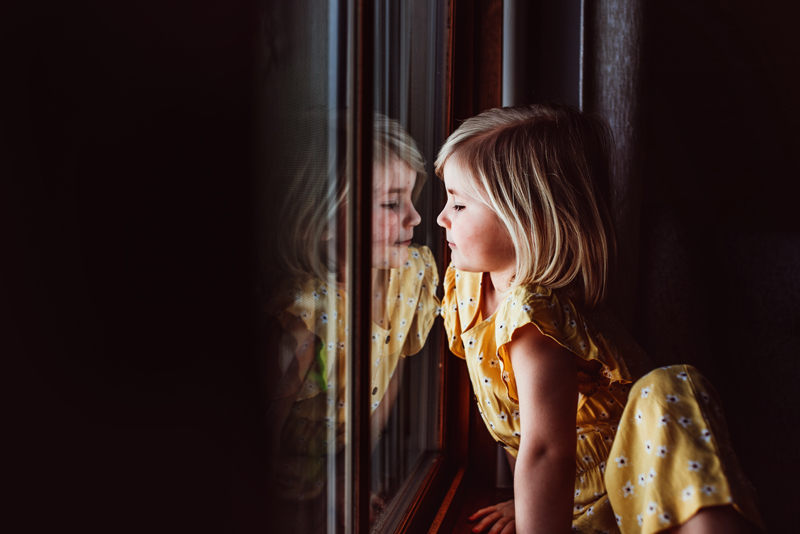 Family Photographer, a little girl in a yellow dress stares out the window, her reflection is mirrored by the glass