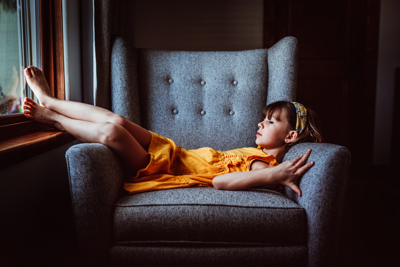 Family Photographer, little girl in a yellow dress lays across a blue chair, her bare feet touching a window