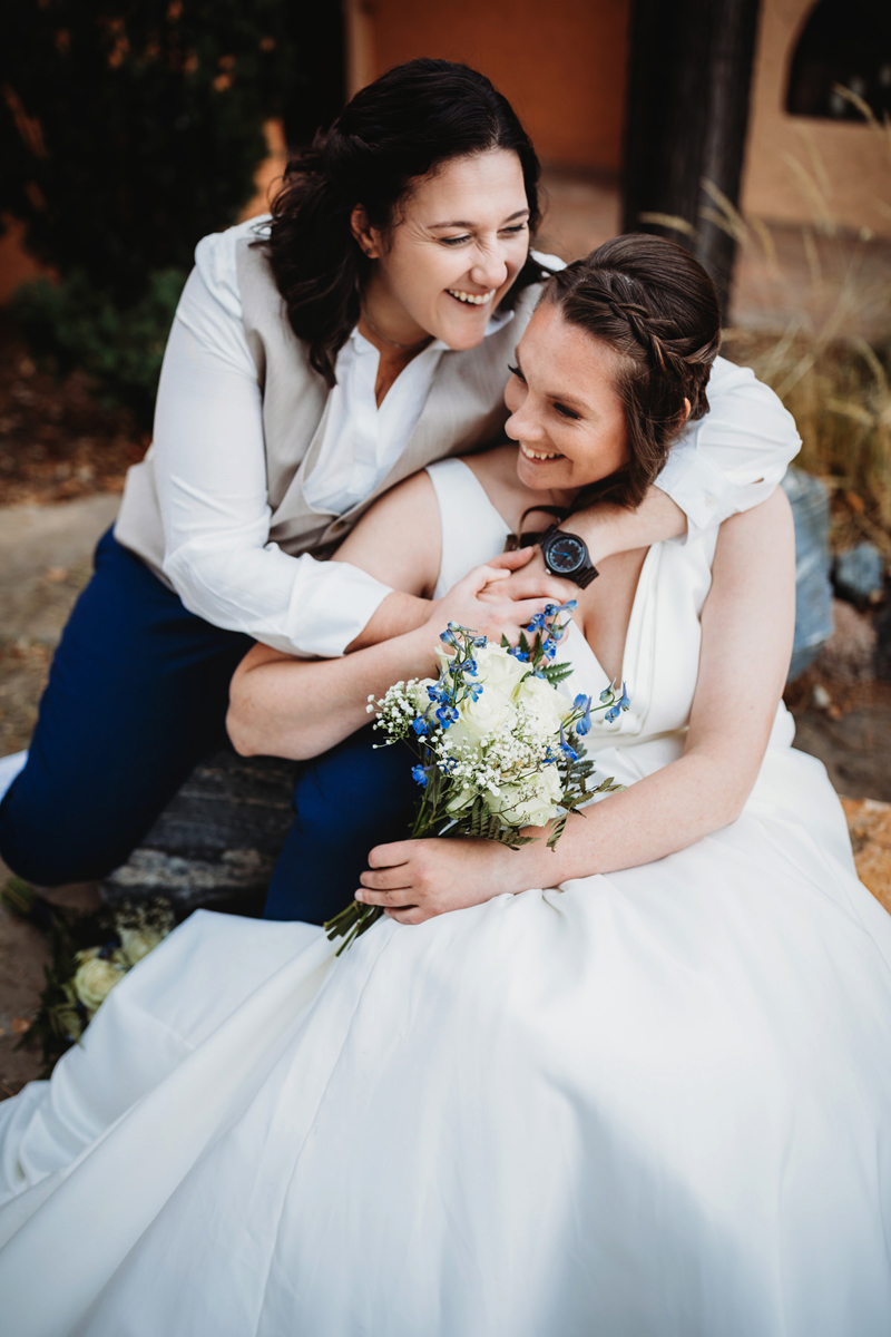 LGBTQ+ Wedding, two happy brides hold each other close and smile