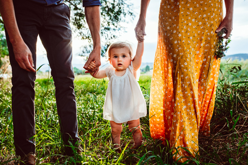 Family Photographer, baby girl in white dress holds parents hands through grass